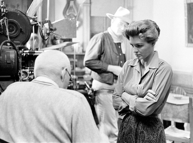 Angie Dickinson talks to director Howard Hawks while John Wayne looks on during the filming of 'Rio Bravo'
