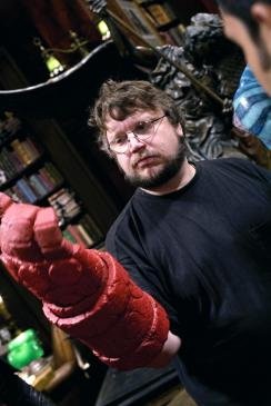 Writer and director Guillermo del Toro tries on Hellboy's right hand of doom on the set of Hellboy II: The Golden Army