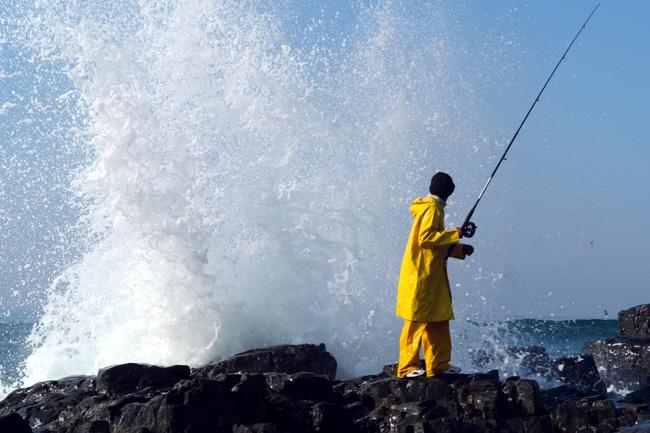 Breaking surf sprays behind a fisherman on the rocks of Sezela Beach, KwaZulu-Natal in the IMAX film Wild Ocean 3-D