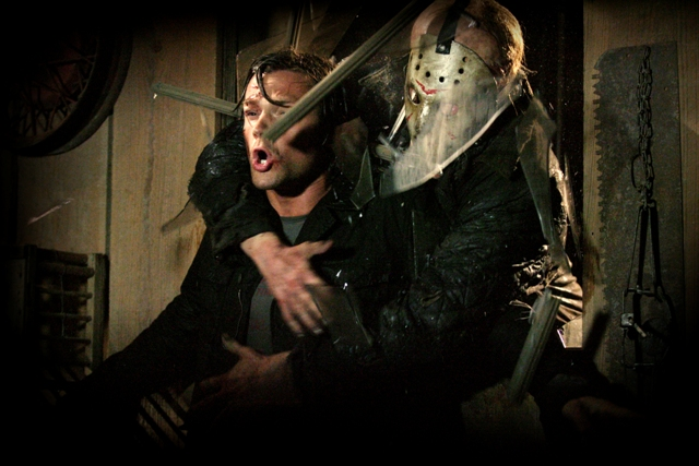 Jason (Derek Mears, right) crashes through a window and grabs Clay (Jared Padalecki, left).