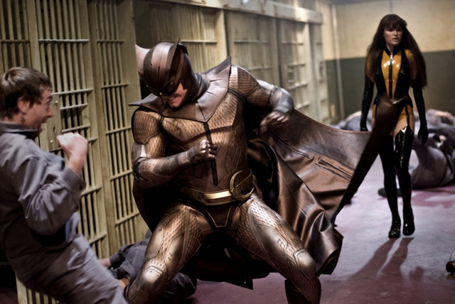 Nite Owl II (Patrick Wilson) fights off a rioting prisoner as Silk Spectre II (Malin Akerman) lends a hand.
